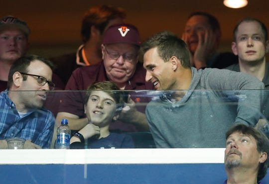 Minnesota Vikings quarterback Kirk Cousins, right, who played at Michigan State, talks with others while watching the first half of an East Regional semifinal between Michigan State and LSU in Washington. D.C.