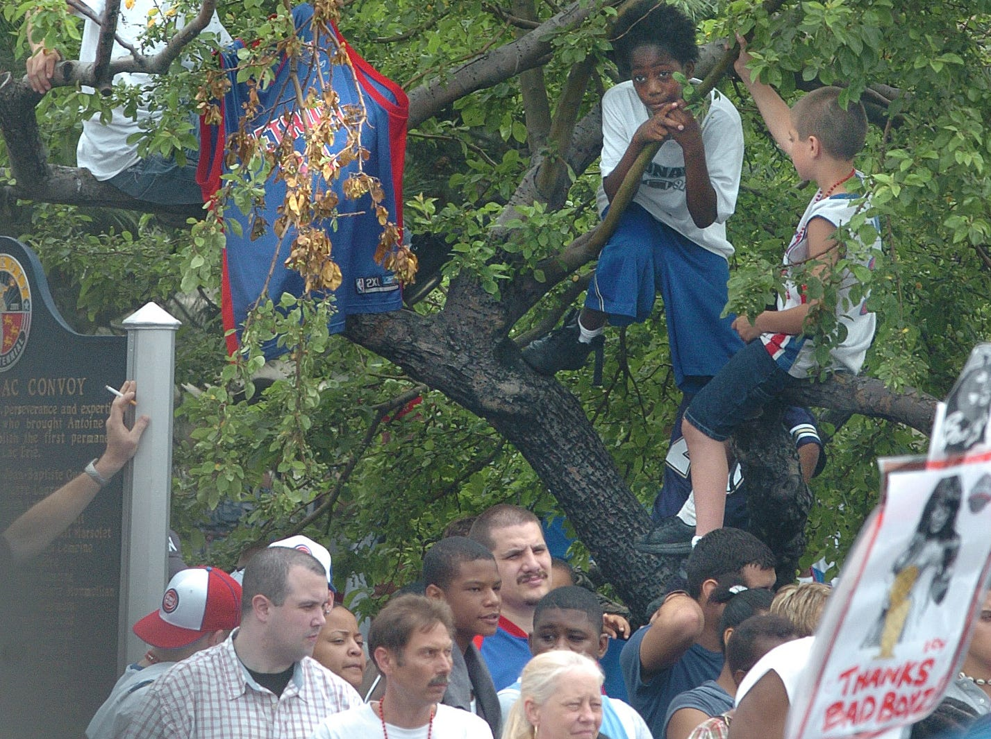 Kids climb up into the trees in Hart Plaza for a better view.