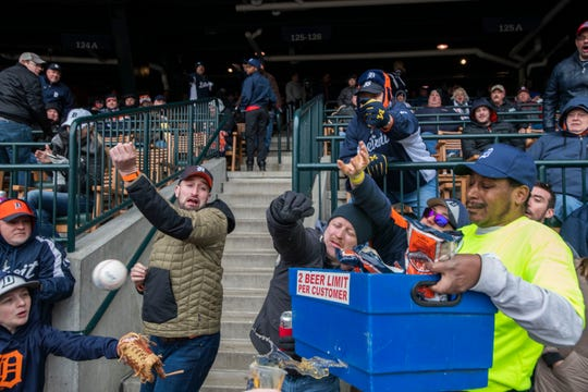 A peanut vendor gets caught in the middle of a group of fans going after a Miguel Cabrera foul ball in the seventh inning. Thirteen year-old Justin Michajlyszyn of Chesterfield Township, lower left, would snag the bouncing ball in the glove he brought to Opening Day for just that purpose.