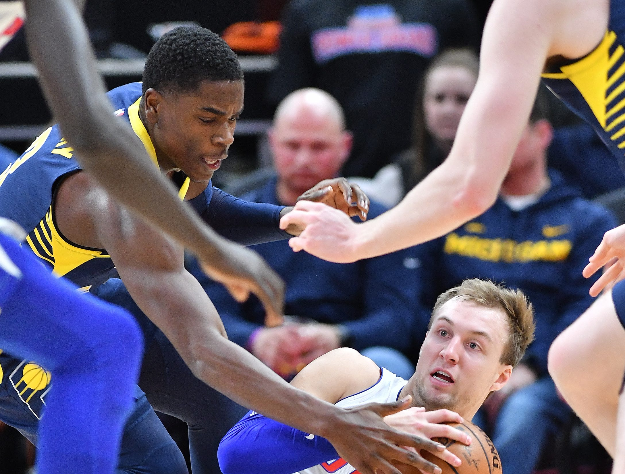 Pistons' Luke Kennard fights for a loose ball with Pacers' Aaron Holiday in the second quarter.