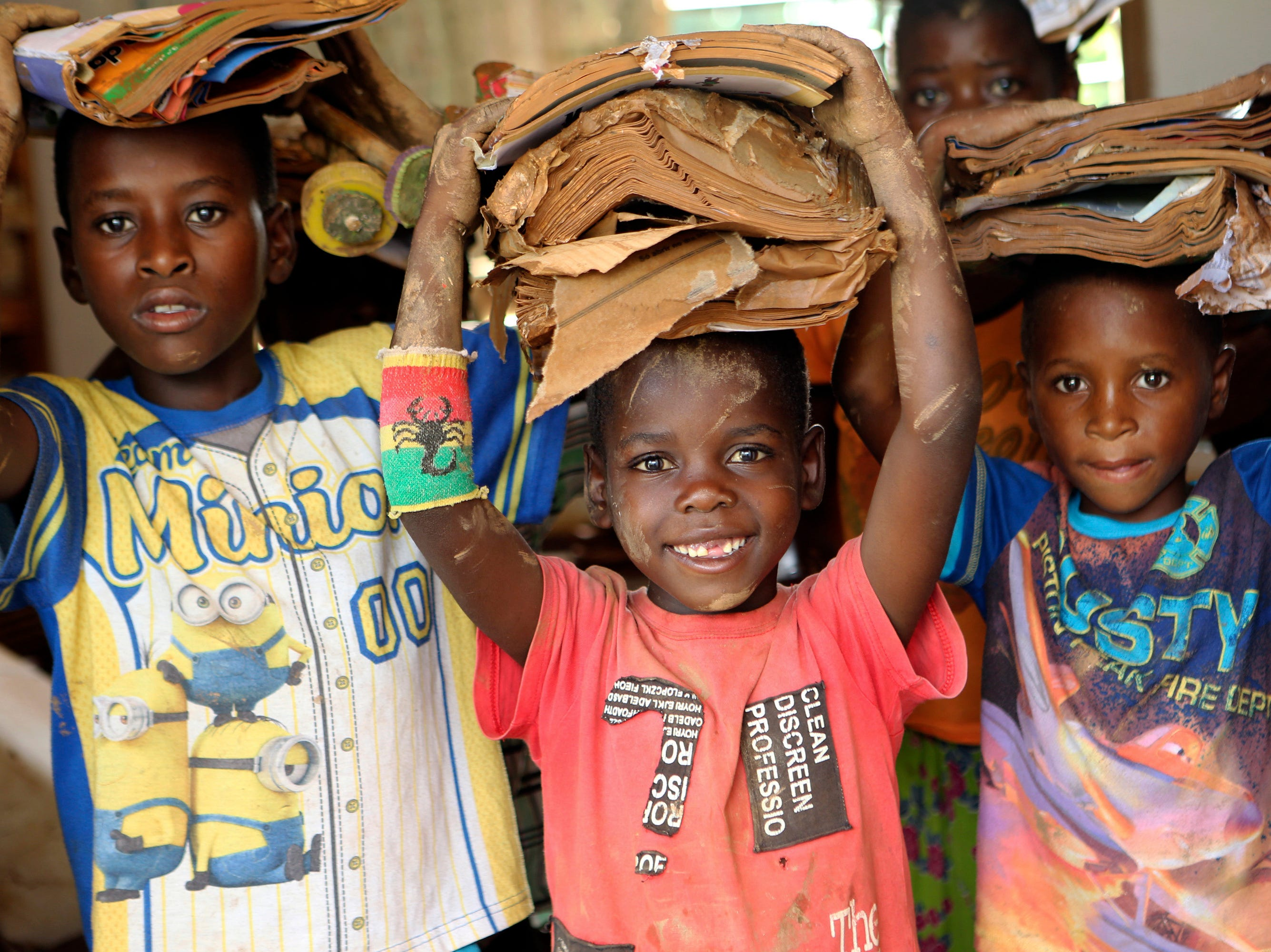Children carry books damaged by the cyclone at a camp for displaced survivors of cyclone Idai in Dombe, about 280km west of Beira, Mozambique, Thursday, April 4, 2019. The Indian Ocean port of Beira, a city of 500,000, is where most of the more than 1,400 cases of cholera have been reported since the outbreak was declared a week ago in the aftermath of Cyclone Idai. Mozambican authorities have reported two deaths so far from the acute diarrheal disease, which can kill within hours if not properly treated.