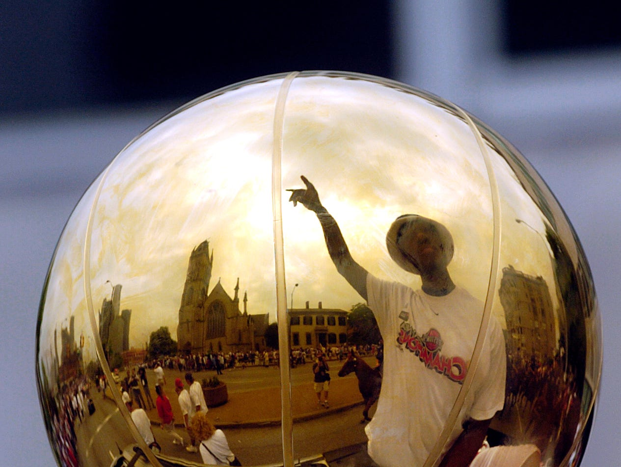 Ben Wallace is reflected in the NBA championship trophy during the parade on Thursday, June 17, 2004.