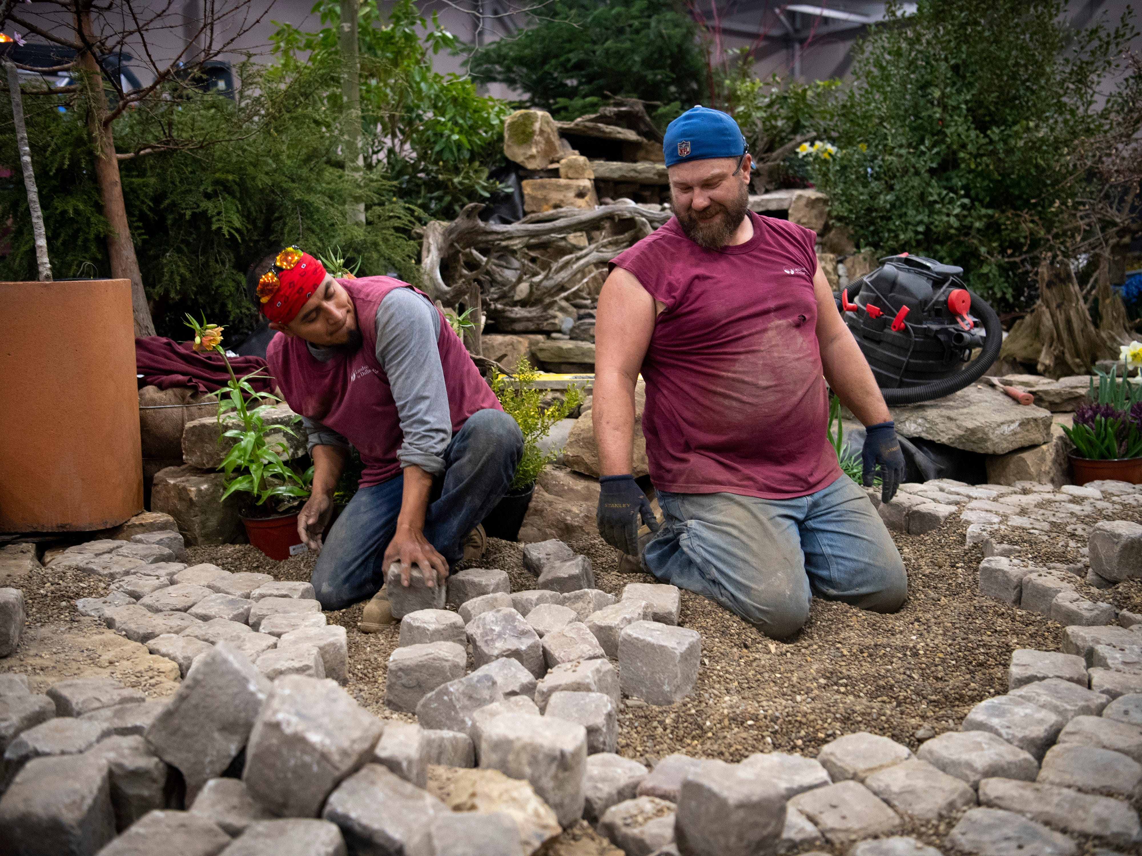 """Frederico Gabino, left, and Kelly Wright, employees with Landscapes by Dallas Foster, lay cobblestones in preparation for the 72nd annual Heritage Federal Credit Union Home Show at Old National Events Plaza Thursday afternoon. The home show runs Saturday through Sunday and costs $5 at the door. Pete Nelson of Animal Planet's """"Treehouse Masters"""" show, and Clint Harp of HGTV's """"Fixer Upper"""" and """"DIY's Wood Work"""", will appear at the event."""