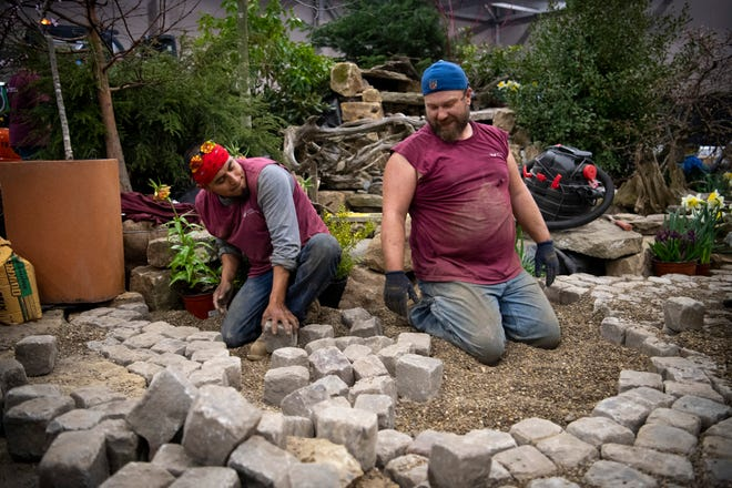 Frederico Gabino, left, and Kelly Wright, employees with Landscapes by Dallas Foster, lay cobblestones in preparation for the 72nd annual Heritage Federal Credit Union Home Show at Old National Events Plaza in 2019. The event wasn't held in 2020, but the 73rd annual event will return Aug. 14-15.