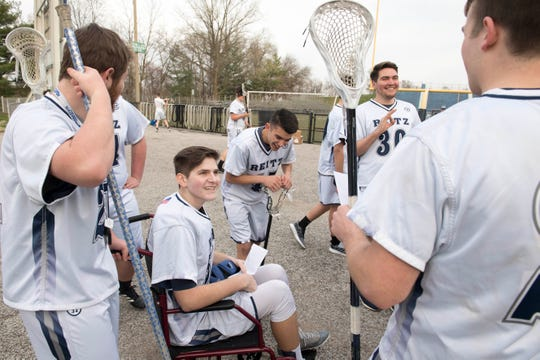 Konner Kolb (53) chats with friends as the Reitz lacrosse team gathers for a team photo Wednesday, April 4, 2019.