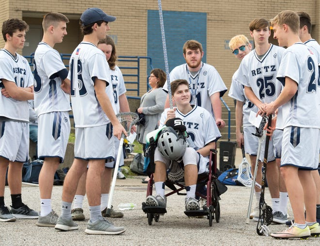 Konner Kolb, center, chats with friends as the Reitz lacrosse team gathers for a team photo Wednesday, April 4, 2019.