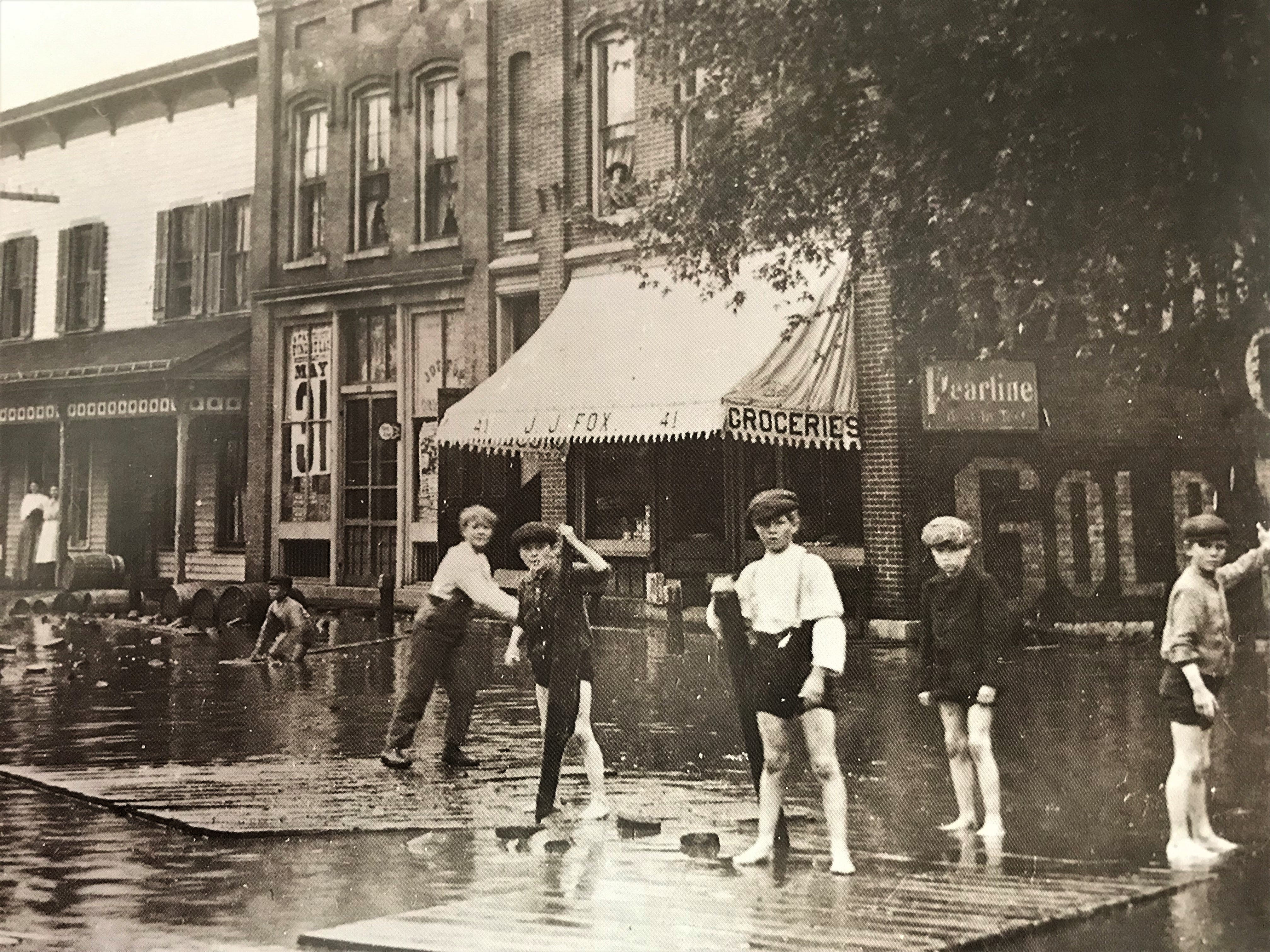 Children traveled the streets of Fond du Lac on sections of floating sidewalk following the flood of June 6, 1905. The dam at Eldorado - on the west branch of the Fond du Lac River - burst, causing flood waters to rush into the city. The photo was taken on Fourth Street, between Main and Marr streets.