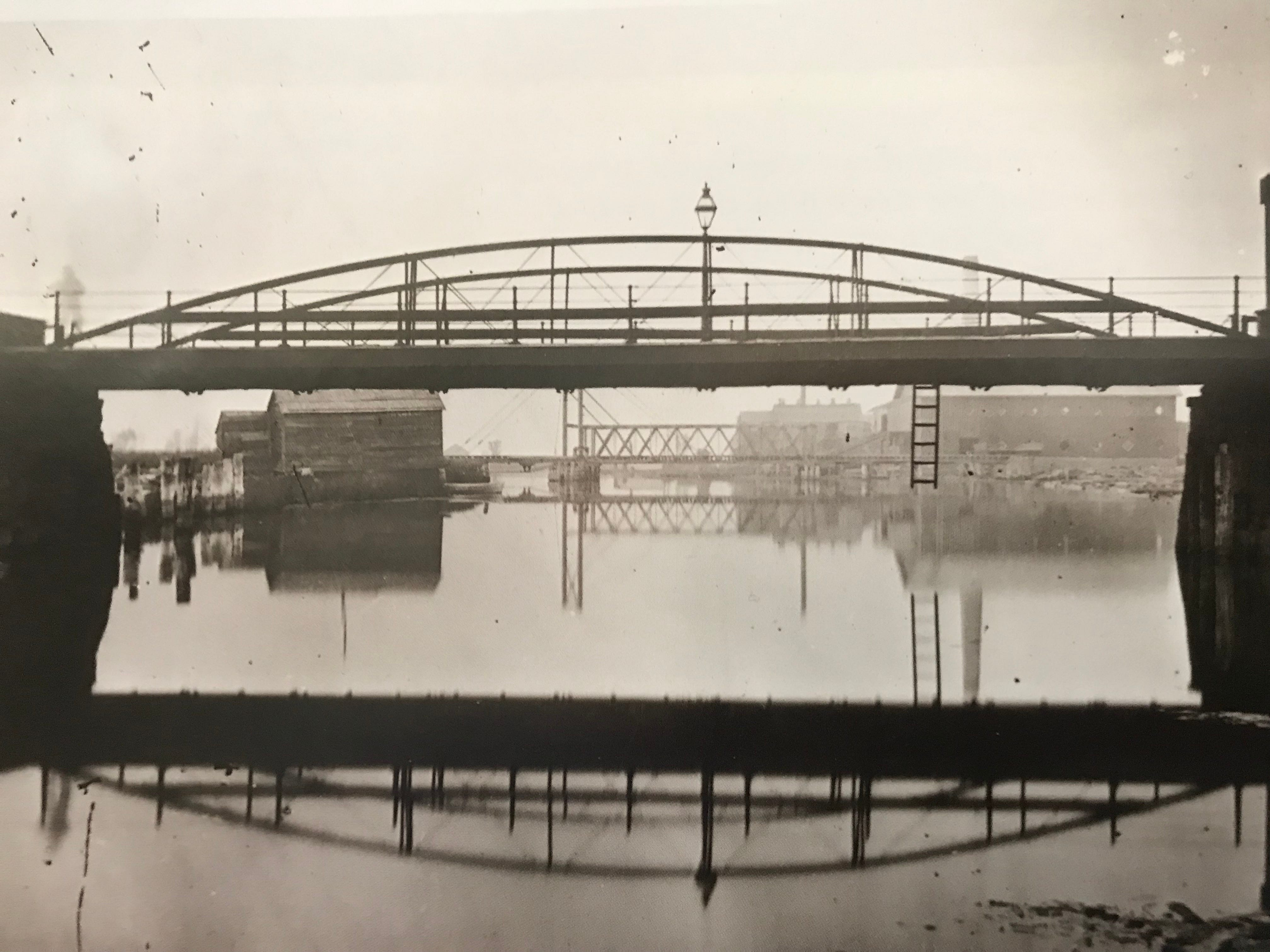 A view of the Scott Street Bridge looking north toward Lake Winnebago in the 1880s. In the background are the Sheboygan & Fond du Lac Railway bridge and a number of lumber mills.