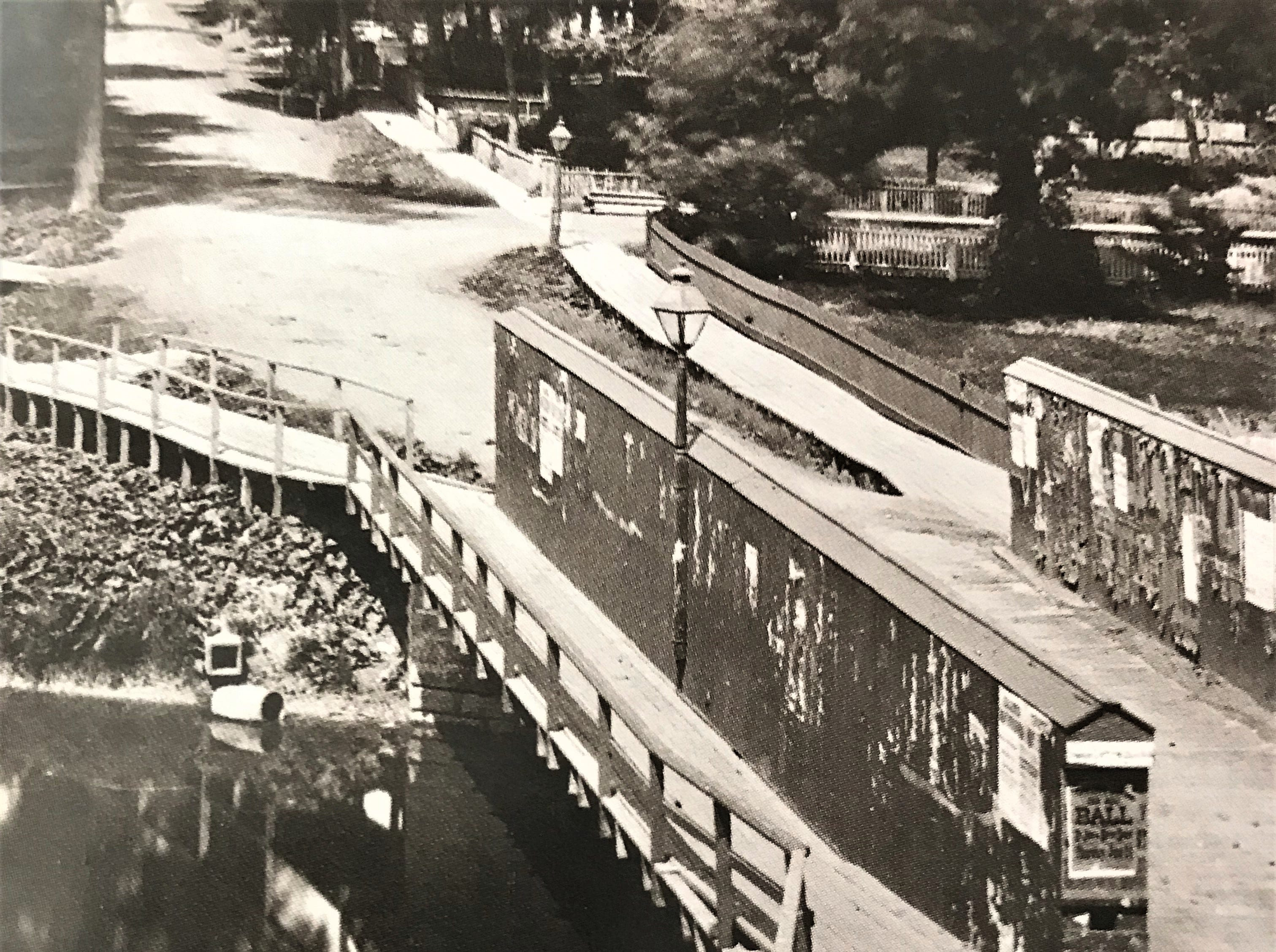 A wooden bridge on Forest Avenue over the east branch of the Fond du Lac River in 1874 , about a block and a half west of Main Street, is representative of bridges in Fond du Lac in the 1870s. Handbills are attached to the wall of the bridge.