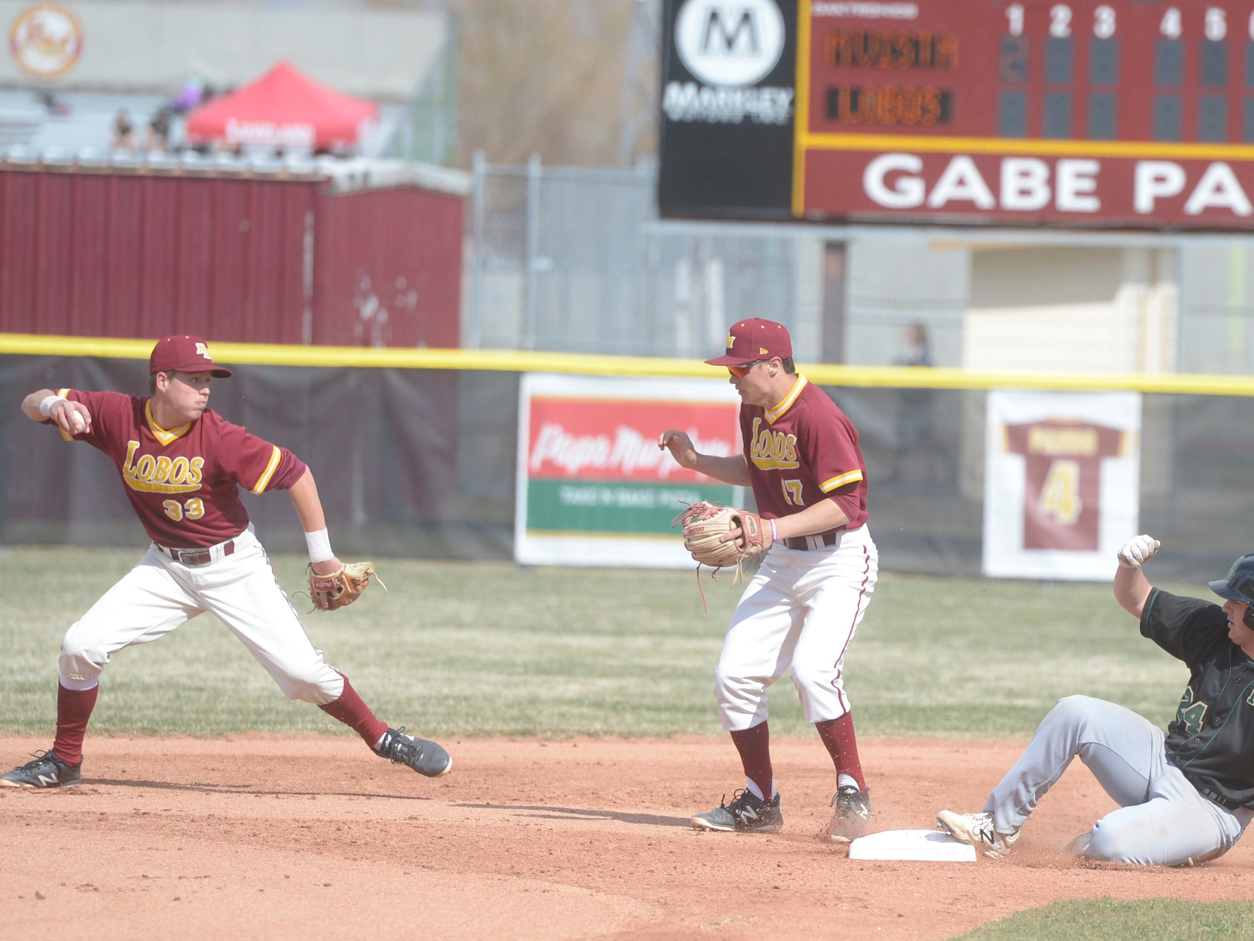 Rocky Mountain baseball shortstop Will Vasseur, left, throws to first during a game Wednesday, April 3, 2019 against Mountain Vista. Mountain Vista won 10-2.