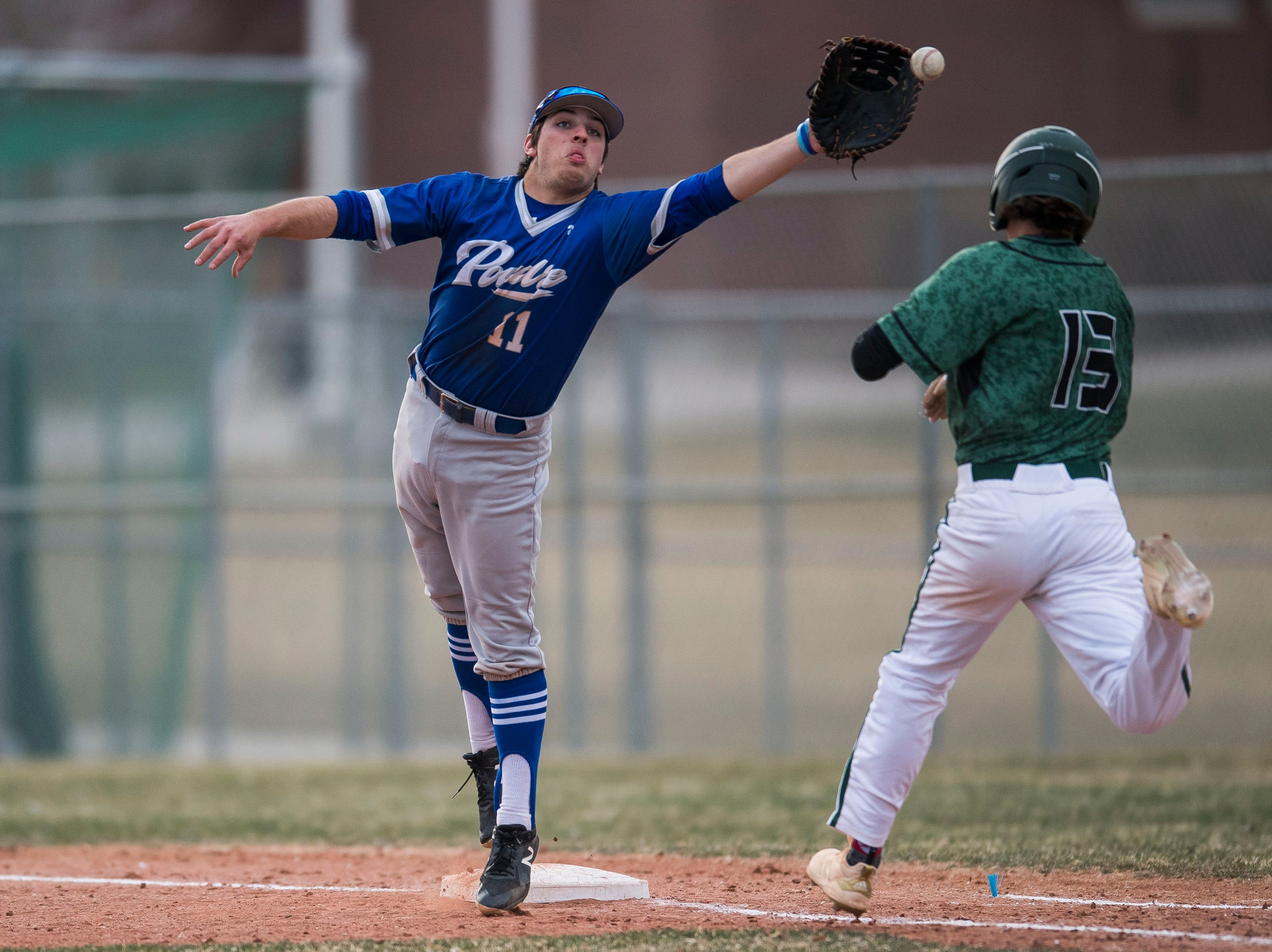 Poudre High School first baseman Jesse Martinez (11) can't reel in the throw from pitcher Sergio Tarango (2) allowing Fossil Ridge High School  runner Jack Cosper (13) to make it to first on Wednesday, April 3, 2019, at Fossil Ridge High School in Fort Collins, Colo.