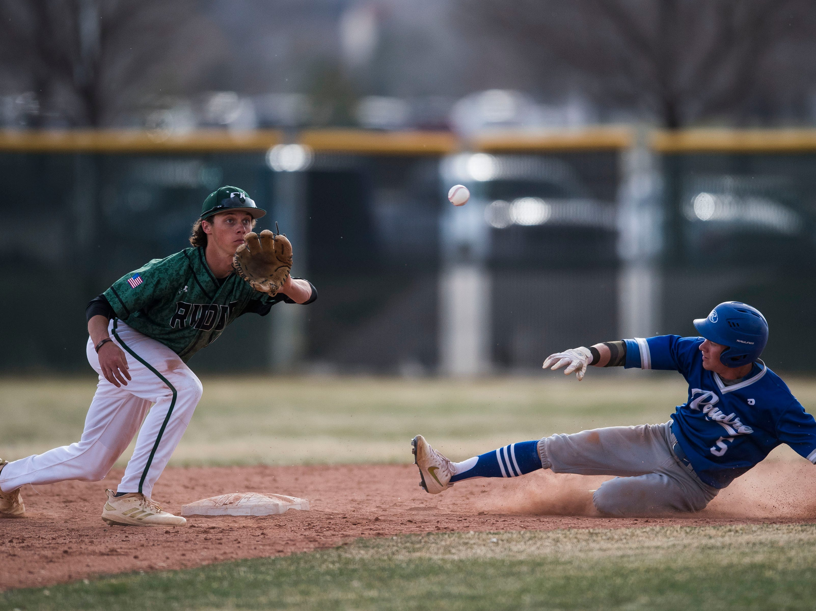 Poudre High School senior Garrett Spaeth (5) slides into second before Fossil Ridge High School second baseman Jack Cosper (13) can tag him out on stolen base on Wednesday, April 3, 2019, at Fossil Ridge High School in Fort Collins, Colo.