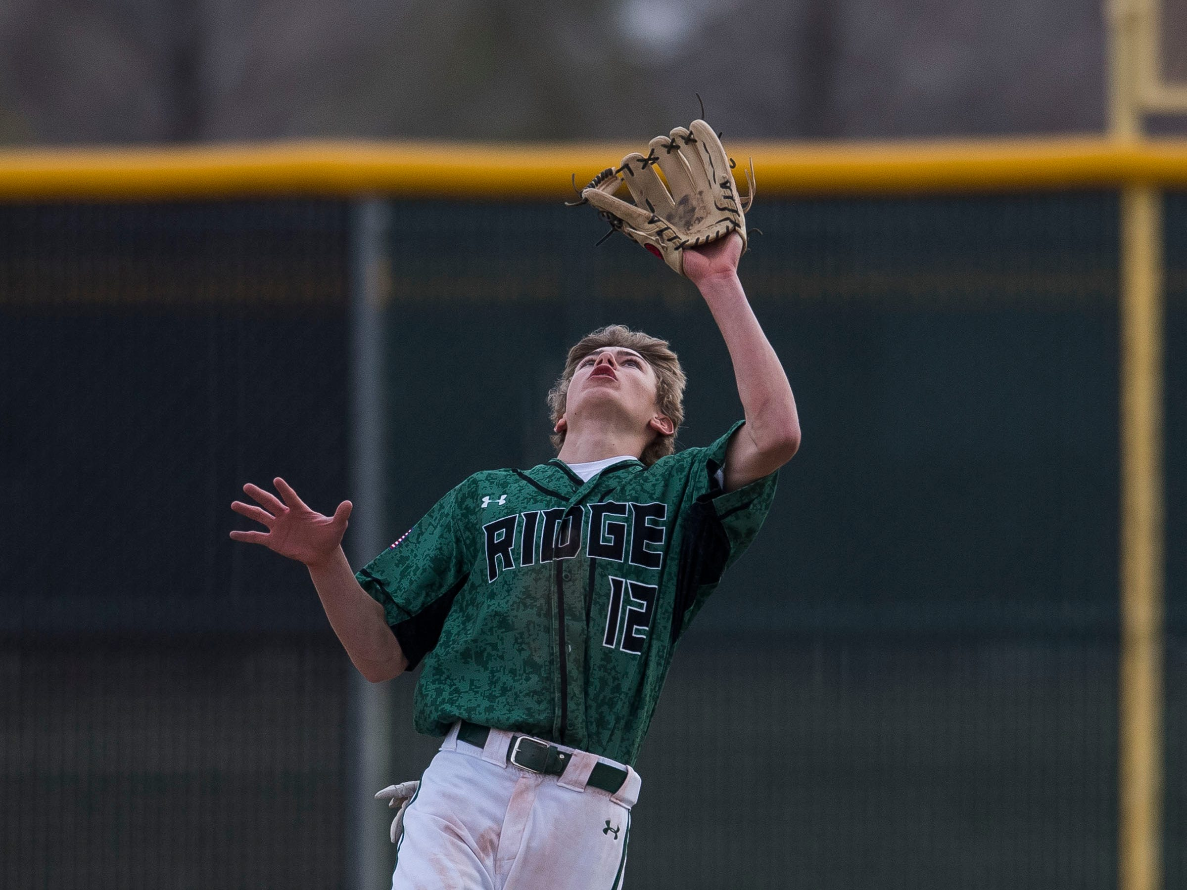 Fossil Ridge High School outfielder Ridge Bowolick (12) looks in a fly foul ball after losing his hat during a game against Poudre High School on Wednesday, April 3, 2019, at Fossil Ridge High School in Fort Collins, Colo.