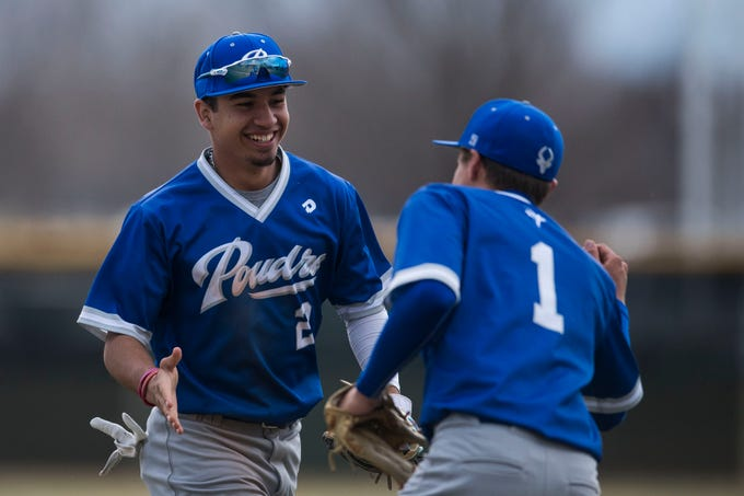 Poudre High School shortstop Sergio Tarango (2) is greeted by pitcher Lee McKinney (1) during a game against Fossil Ridge High School on Wednesday, April 3, 2019, at Fossil Ridge High School in Fort Collins, Colo.
