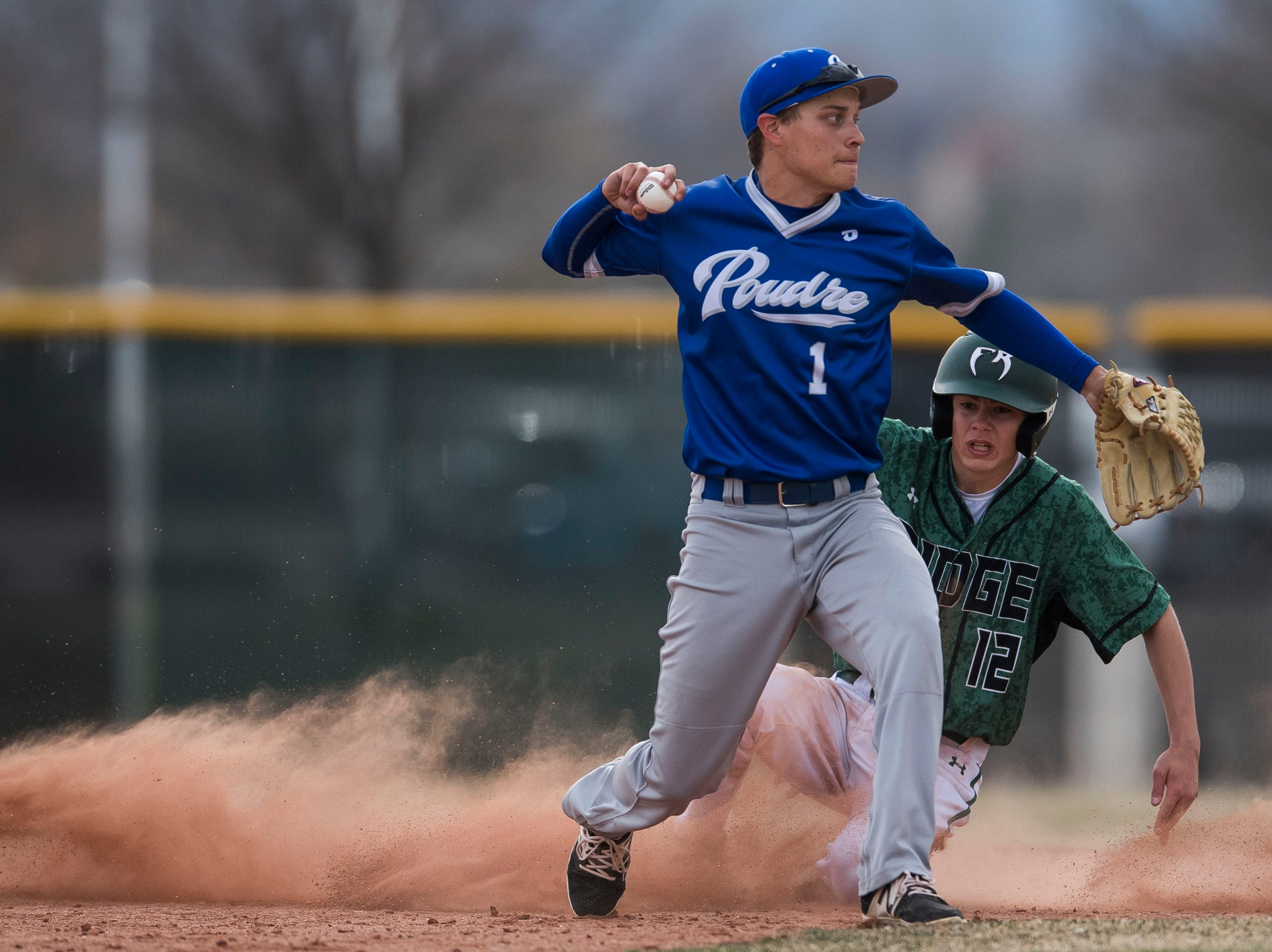 Poudre High School second baseman Lee McKinney (1) pulls down the double play after forcing out Fossil Ridge High School runner Ridge Bowolick (12) at second on Wednesday, April 3, 2019, at Fossil Ridge High School in Fort Collins, Colo.