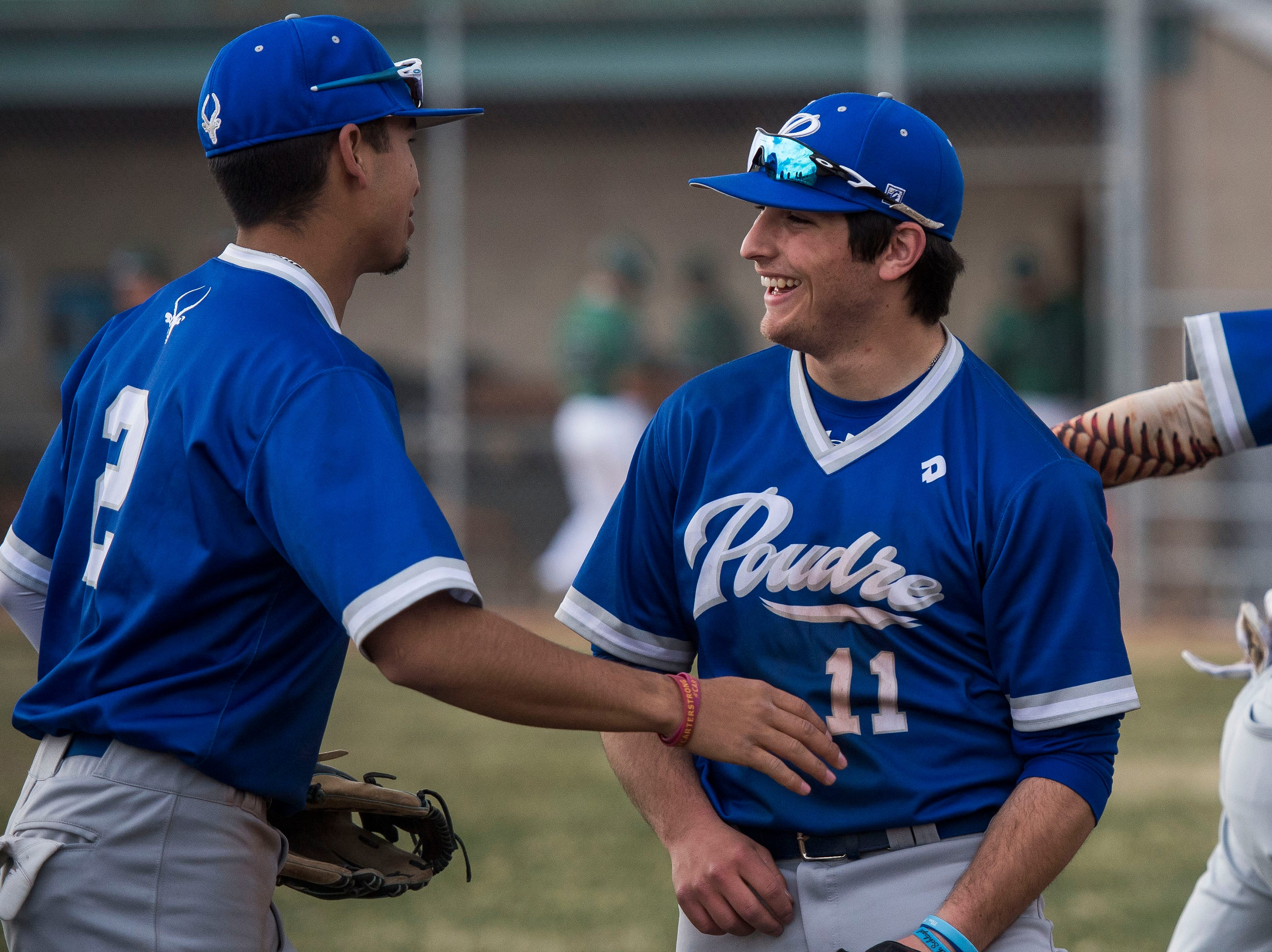 Poudre High School first baseman Jesse Martinez (11) celebrates with shortstop Sergio Tarango (2) during a game against Fossil Ridge High School on Wednesday, April 3, 2019, at Fossil Ridge High School in Fort Collins, Colo.
