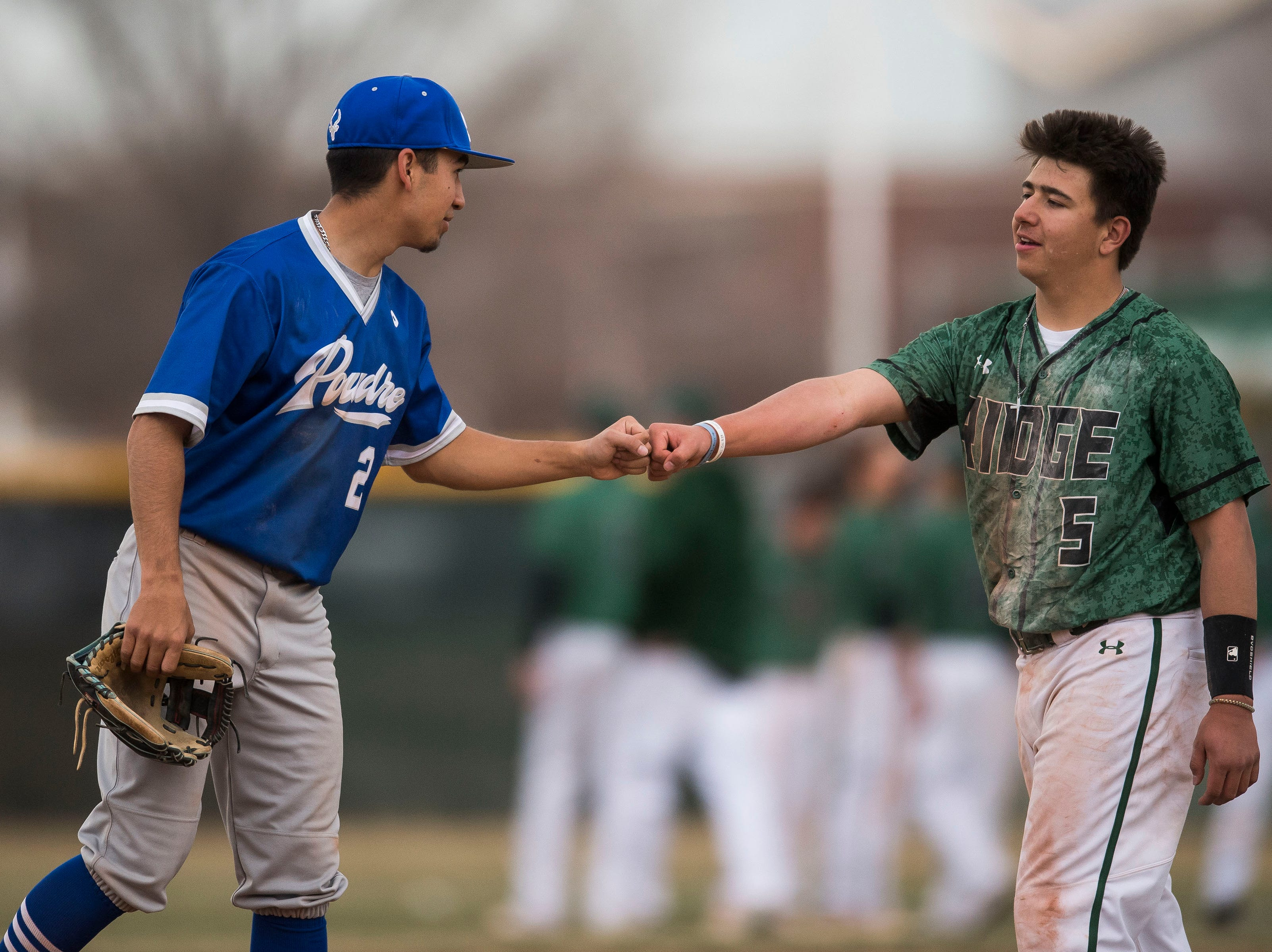 Poudre High School junior Sergio Tarango (2) bumps fists with Fossil Ridge High School's Nathan Novak (5) after a win by Poudre on Wednesday, April 3, 2019, at Fossil Ridge High School in Fort Collins, Colo.