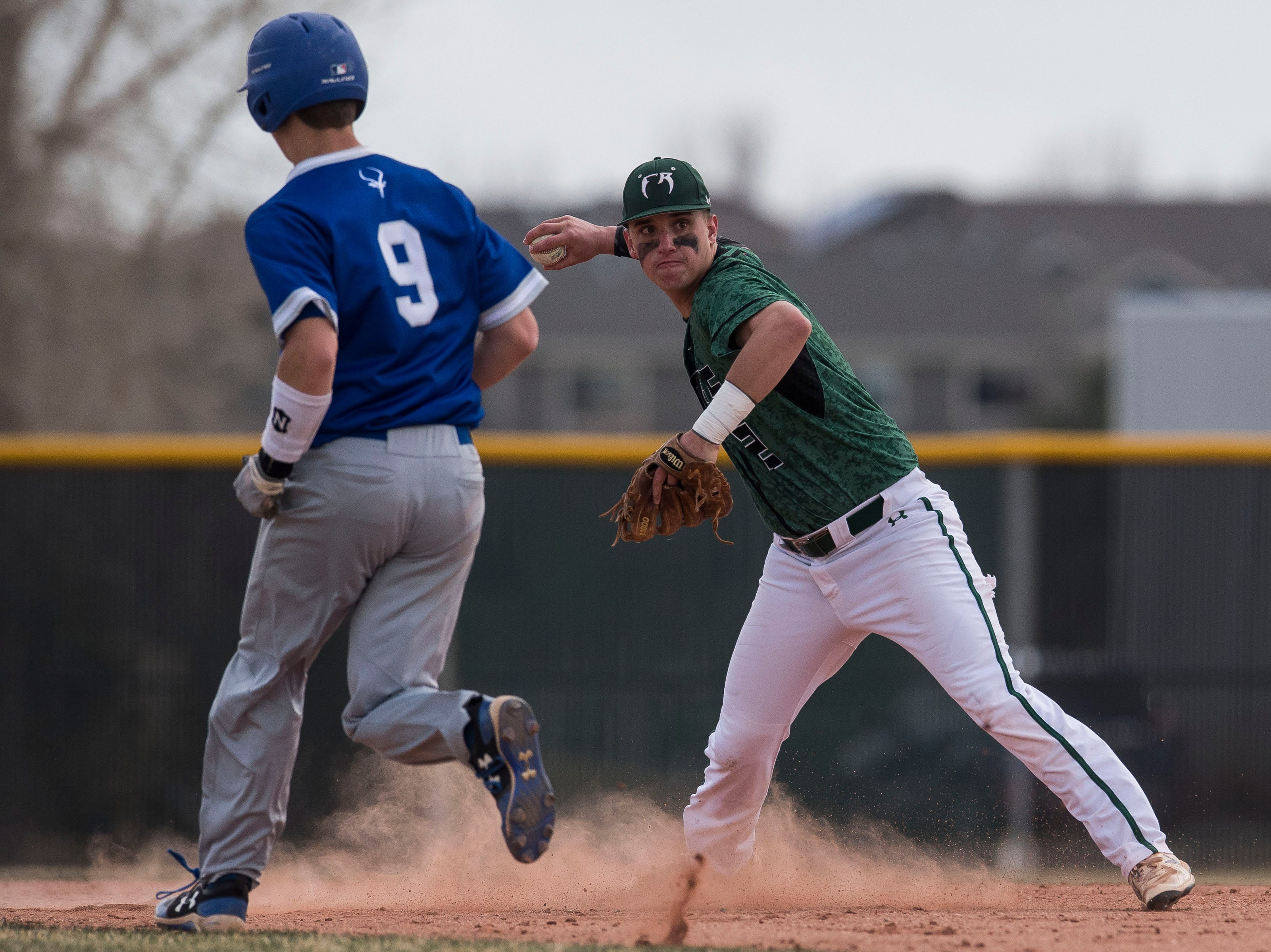 Fossil Ridge High School shortstop Talen Townsend (2) turns two after forcing out Poudre High School runner Zach Pettofrezzo (9) on Wednesday, April 3, 2019, at Fossil Ridge High School in Fort Collins, Colo.