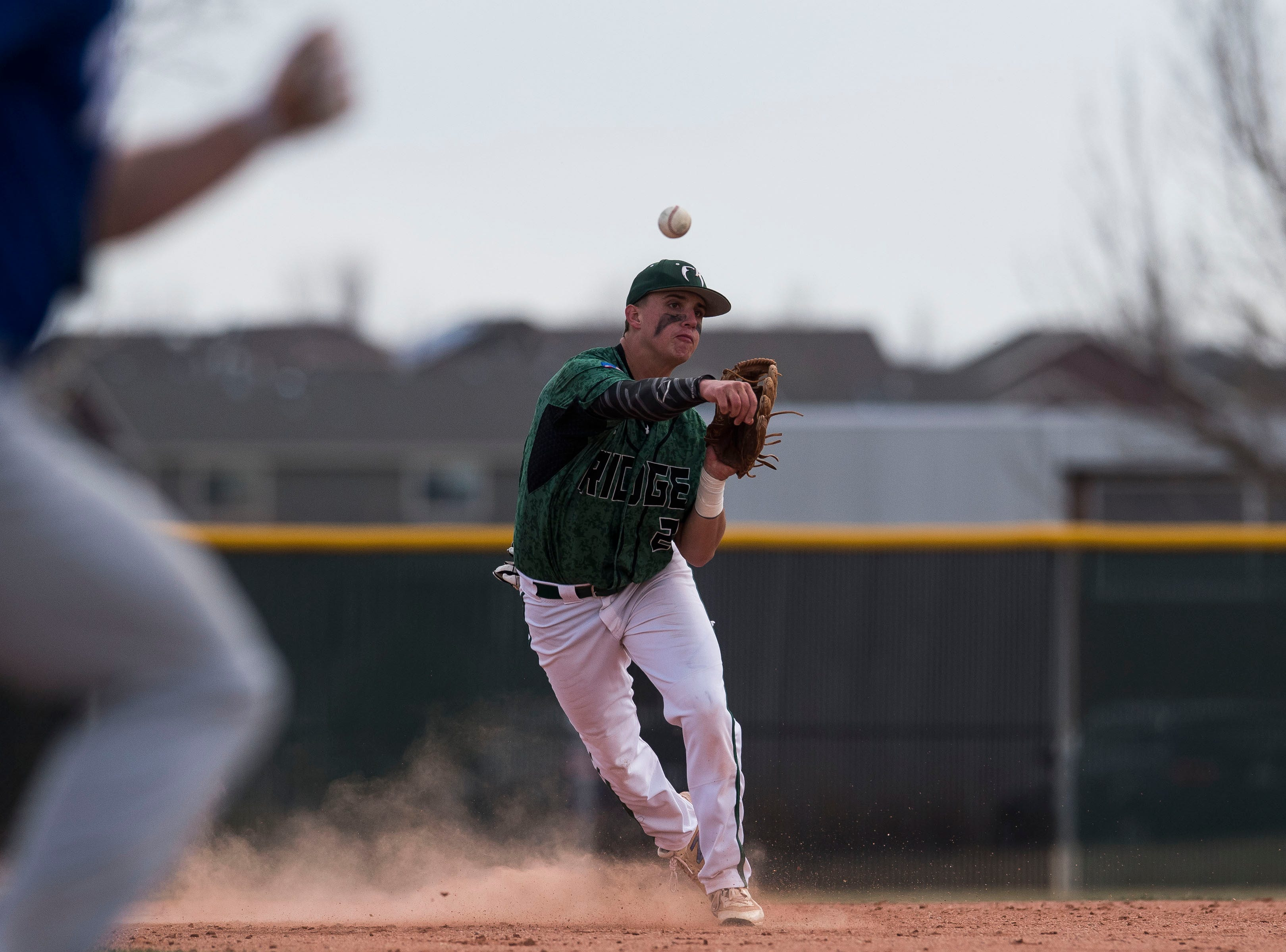 Fossil Ridge High School shortstop Talen Townsend (2) throws out Poudre High School runner Tate Satterfield (4) at first base on Wednesday, April 3, 2019, at Fossil Ridge High School in Fort Collins, Colo.