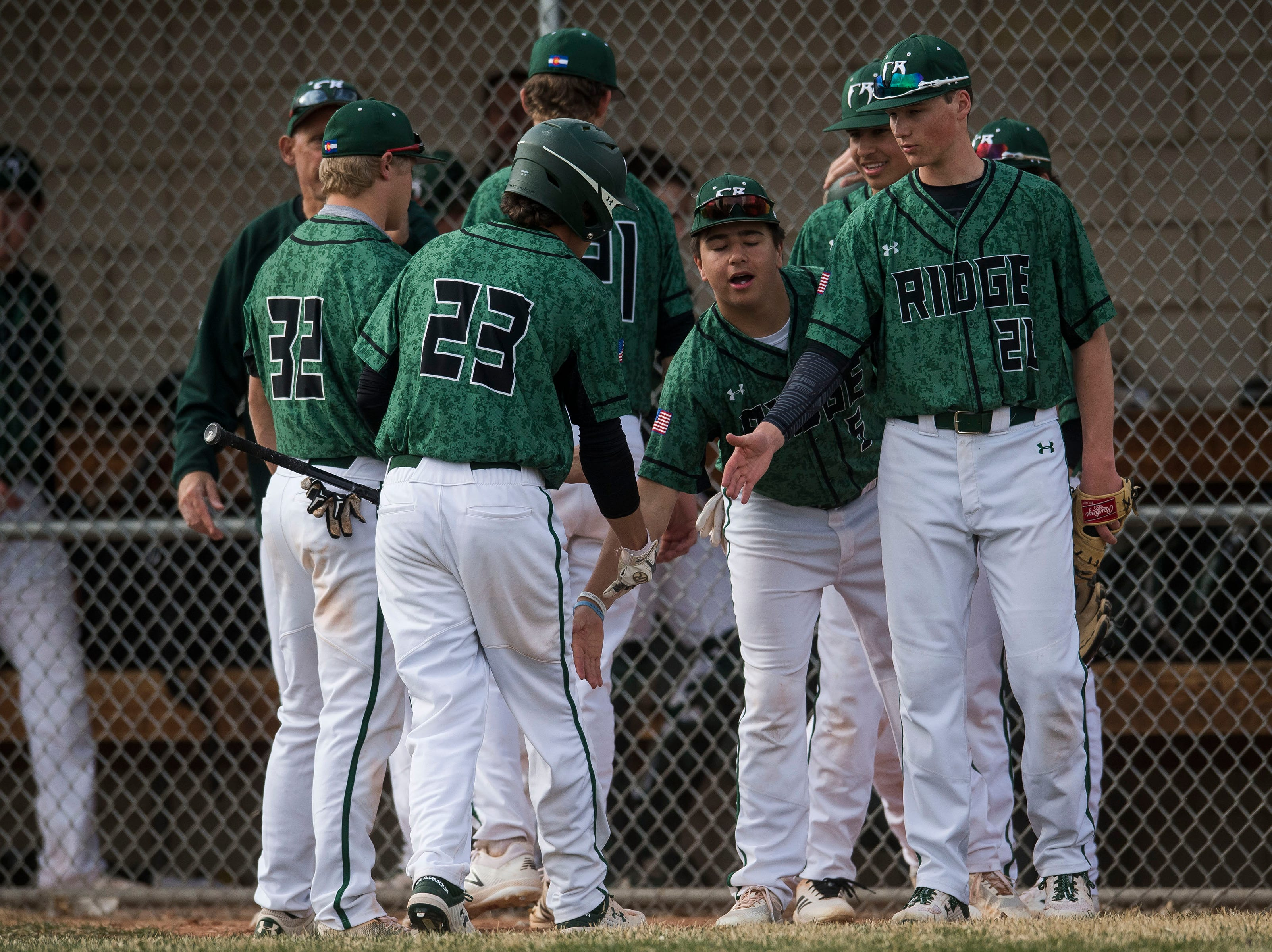 Fossil Ridge High School runner Dillon Henninger (23) is greeted by teammates after scoring against Poudre High School on Wednesday, April 3, 2019, at Fossil Ridge High School in Fort Collins, Colo.