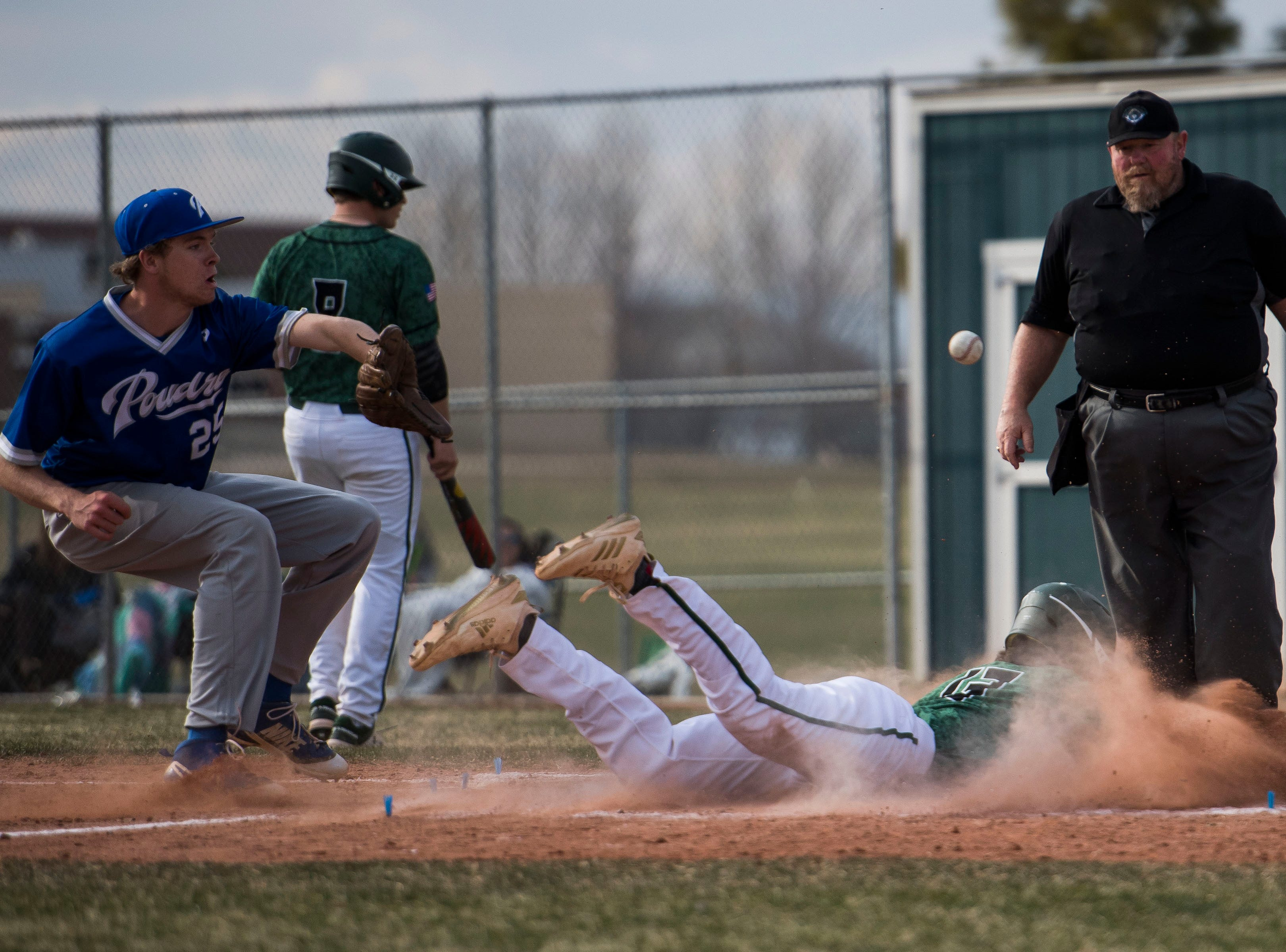 Fossil Ridge High School runner Jack Cosper (13) slides into home before Poudre High School pitcher Chris Wallace (25) can get the tag on Wednesday, April 3, 2019, at Fossil Ridge High School in Fort Collins, Colo.