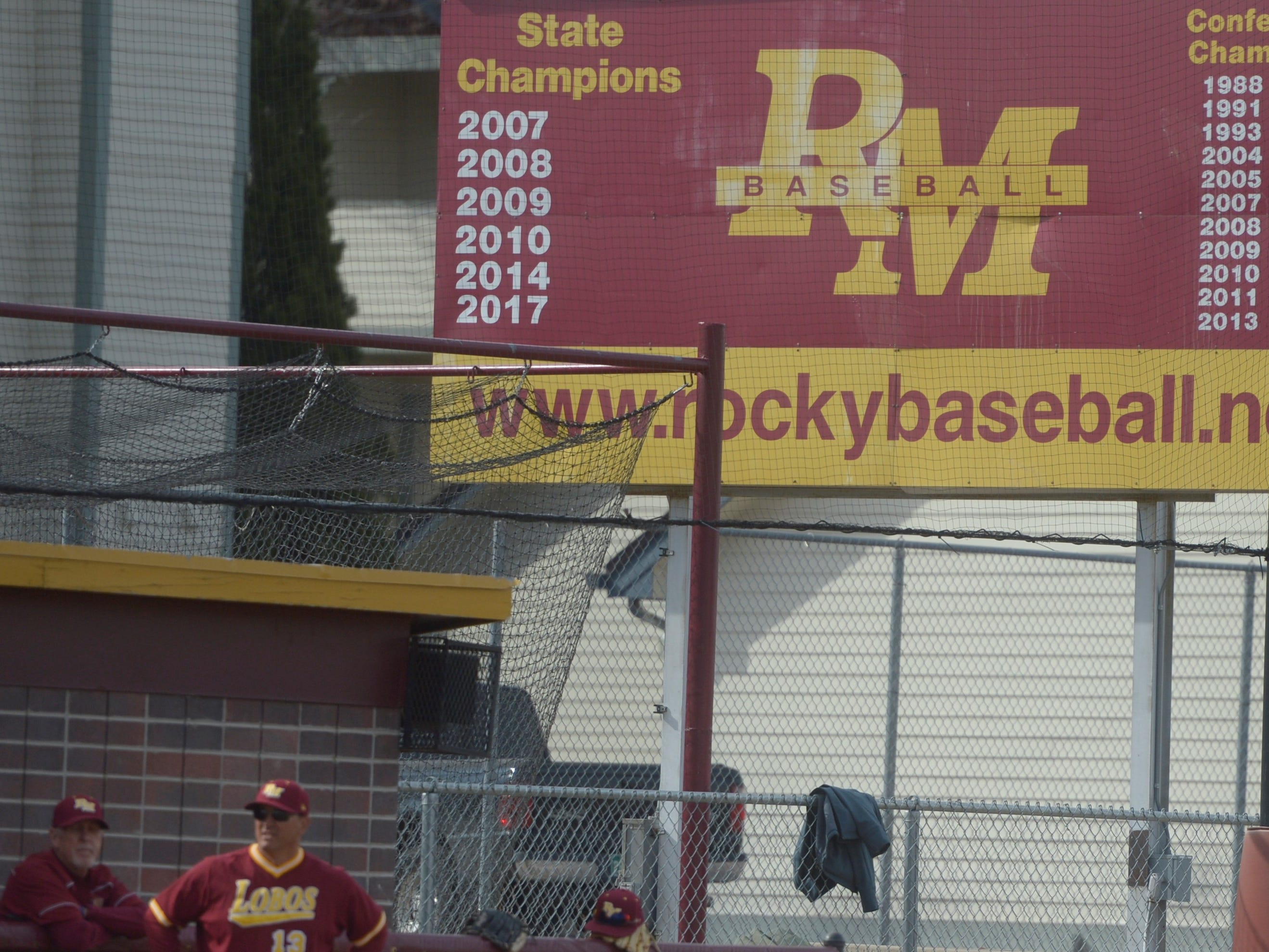 Rocky Mountain baseball coaches Glen Schwab, left, and Scott Bullock stand under the sign showing the Lobos' six state titles during a game Wednesday, April 3, 2019 against Mountain Vista. Mountain Vista won 10-2.