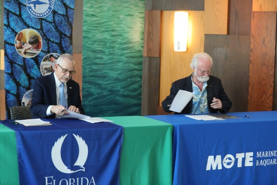 Dr. Michael Crosby (at right), President & CEO of Mote Marine Laboratory, and Dr. James Llorens, provost of Florida Gulf Coast University, sign an agreement confirming their commitment to harmful algal bloom research and education.