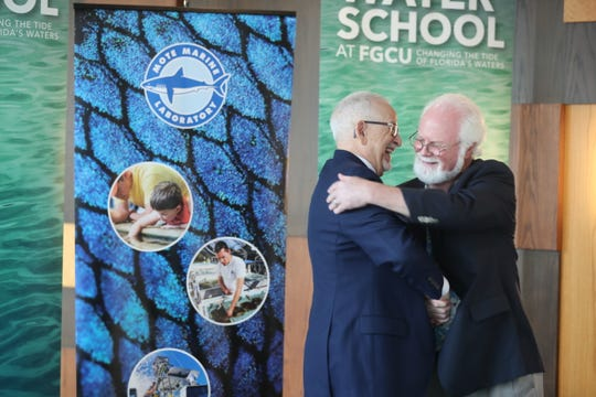(Right)Dr Michael Crosby, President & CEO of mote Marine Laboratory, and Dr James Llorens, provost of Florida Gulf Coast University, hug after signing papers confirming their commitment to harmful algal bloom research and education.  (Andrea Melendez)
