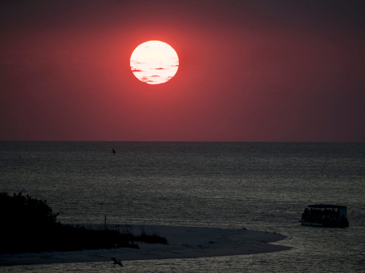 A sunset cruise enjoys the ball of fire before it sets on the horizon at New Pass on the south end of Lovers Key in Bonita Springs on Wednesday April 3, 2019.