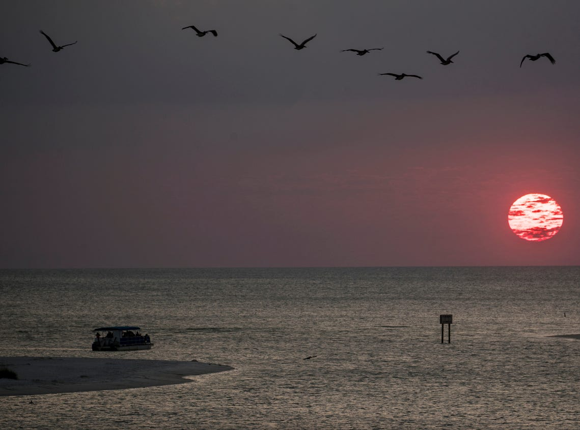 A sunset cruise enjoys the ball of fire before it sets on the horizon at New Pass on the south end of Lovers Key in Bonita Springs on Wednesday, April 3, 2019.