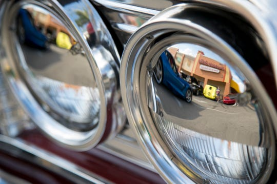 Classic cars at the Hot Chili Rods Cruise-In are reflected in the chrome accents on the headlights of a Chevy Impala on Wednesday, April 3, 2019, in Cape Coral.