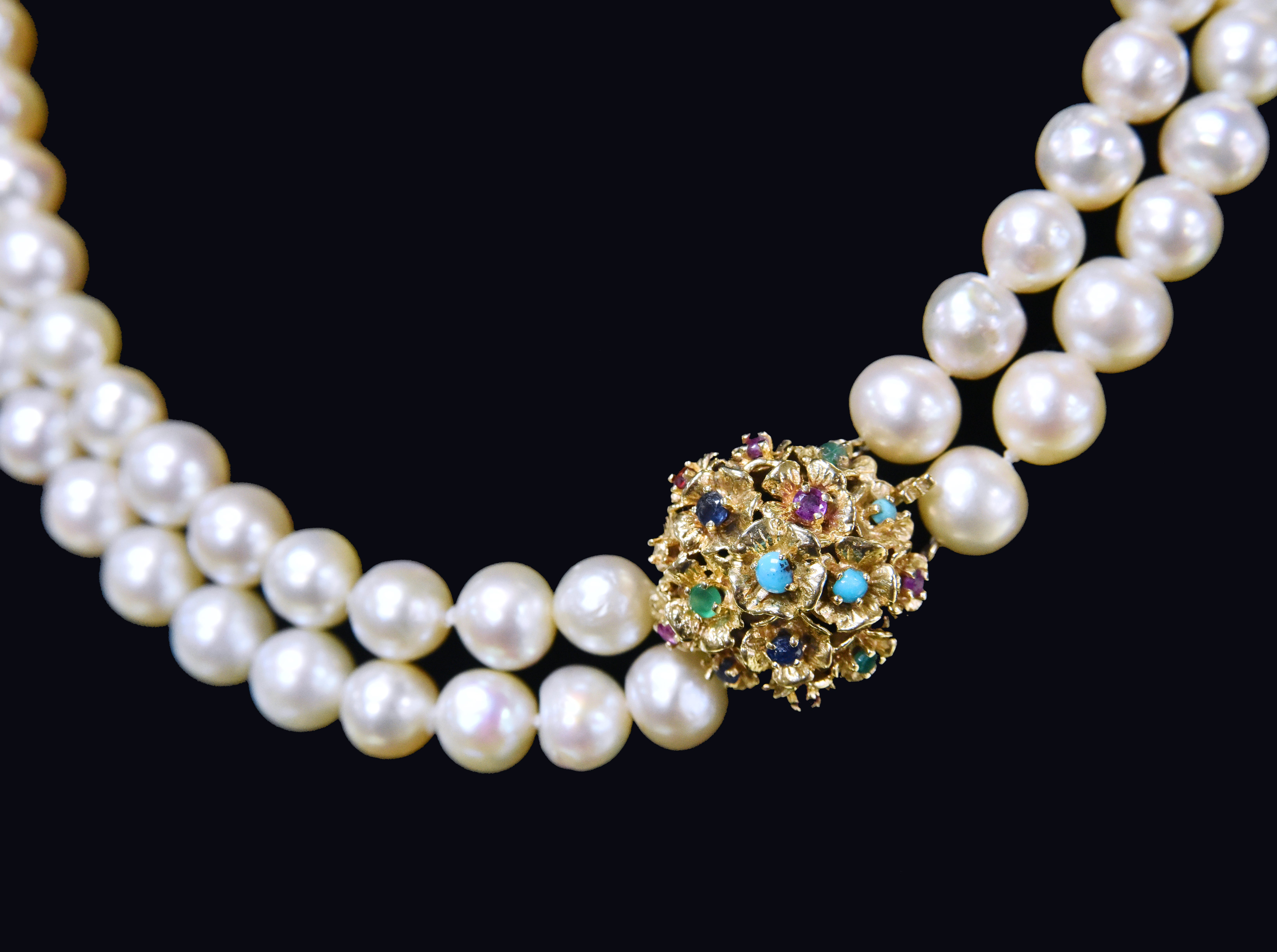 An antique cultured pearl necklace with a 14k decorative clasp with sapphire, emerald, ruby and turquoise.