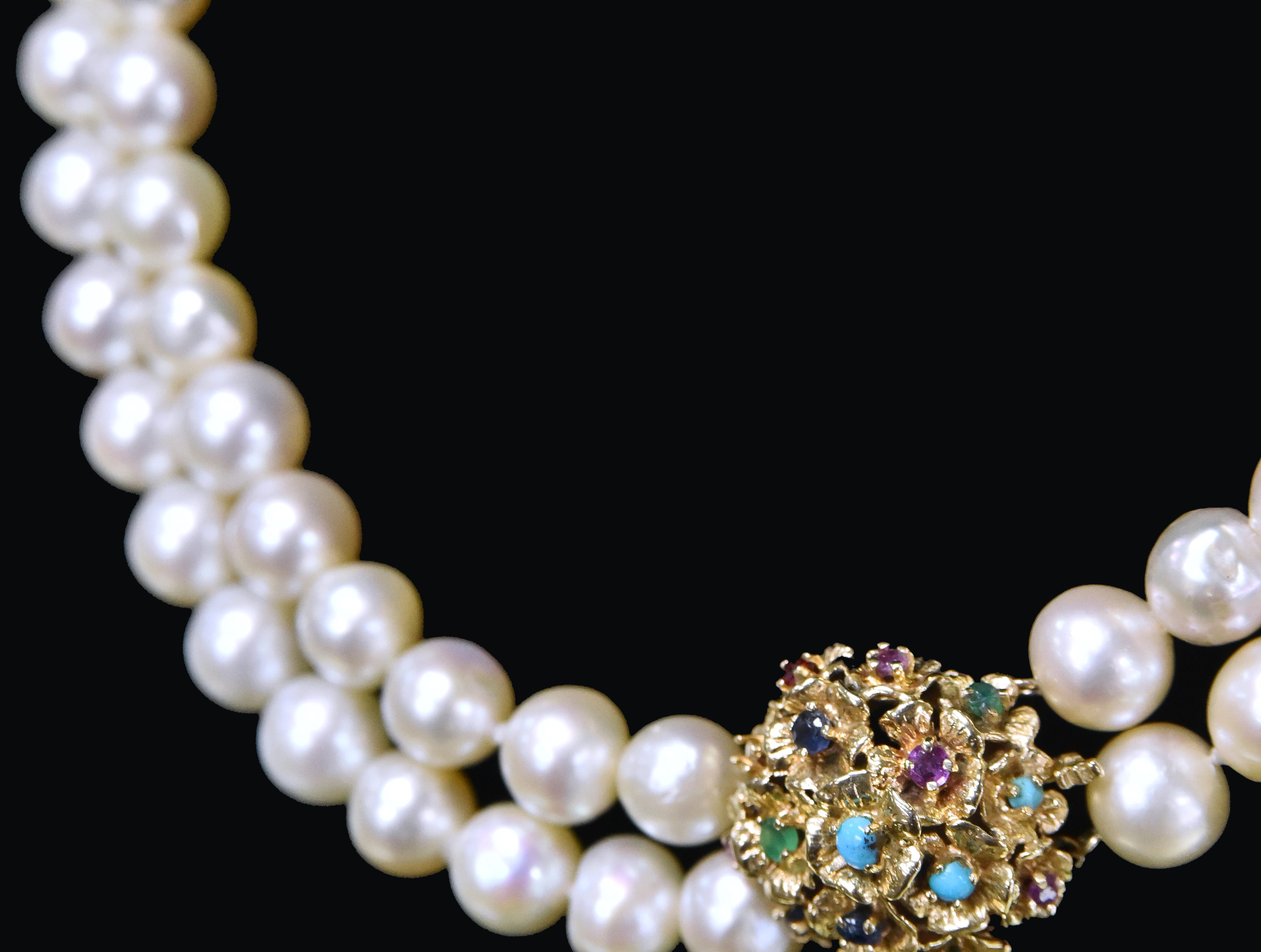 An antique cultured pearl necklace with a 14k decorative clasp with sapphire, emerald, ruby and turquoise from Julie's Jewels and Gifts.