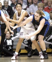 Montana's Dana Conway, left, looks to pass as North Carolina-Asheville's Stacy Shepard tries to grab the ball on Dec. 29, 2005.