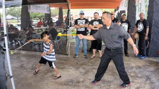 DLX brother Senator Frank Aguon Jr. emulates Josiah Nehemiah Lujan Perez's sling shot technique during the DLX event. Perez (Sling Team Guam) was the 2018 Champion in youth division of the International Slinging Competition in Mallorca, Spain.