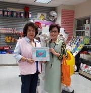 Yeon Sook Park donated Color Guam in Moving Colors, coloring books on March 22 to the Guam Memorial Hospital Volunteer Association's 54th Anniversary Charity Ball. Pictured: Lina McDonald, Guam Memorial Hospital Volunteer Association Gift Shop manager.