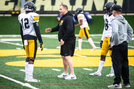 Iowa linebackers coach Seth Wallace works with D.J. Johnson (12) and Matt Hankins (8) during a Hawkeye football spring practice on Thursday, April 4, 2019, at the University of Iowa outdoor practice facility in Iowa City, Iowa.