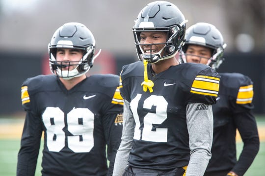 Iowa wide receivers Brandon Smith (12) and Nico Ragaini (89) eye their next drill during an April 4 practice in Iowa City.