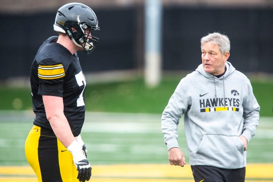Iowa head coach Kirk Ferentz, right, talks with offensive lineman Mark Kallenberger during a Hawkeye football spring practice on Thursday, April 4, 2019, at the University of Iowa outdoor practice facility in Iowa City, Iowa.