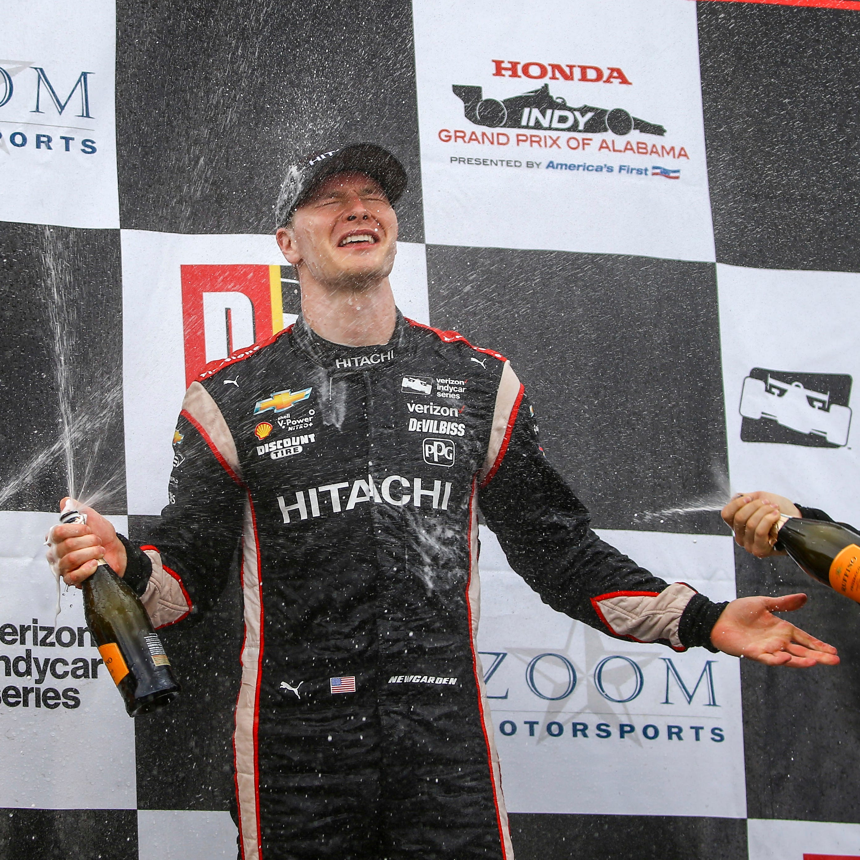 Second place Ryan Hunter-Reay, left, and third placed James Hinchcliffe, right, spray champagne on winner Josef Newgarden after the Honda Indy Grand Prix of Alabama auto race at Barber Motorsports Park, April 23, 2018, in Birmingham, Ala.