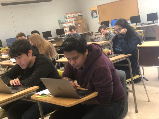 Luis Jimenez and Michael Martinez, front row, and Krysthen Sanchez, behind them, work during computer science class Wednesday.