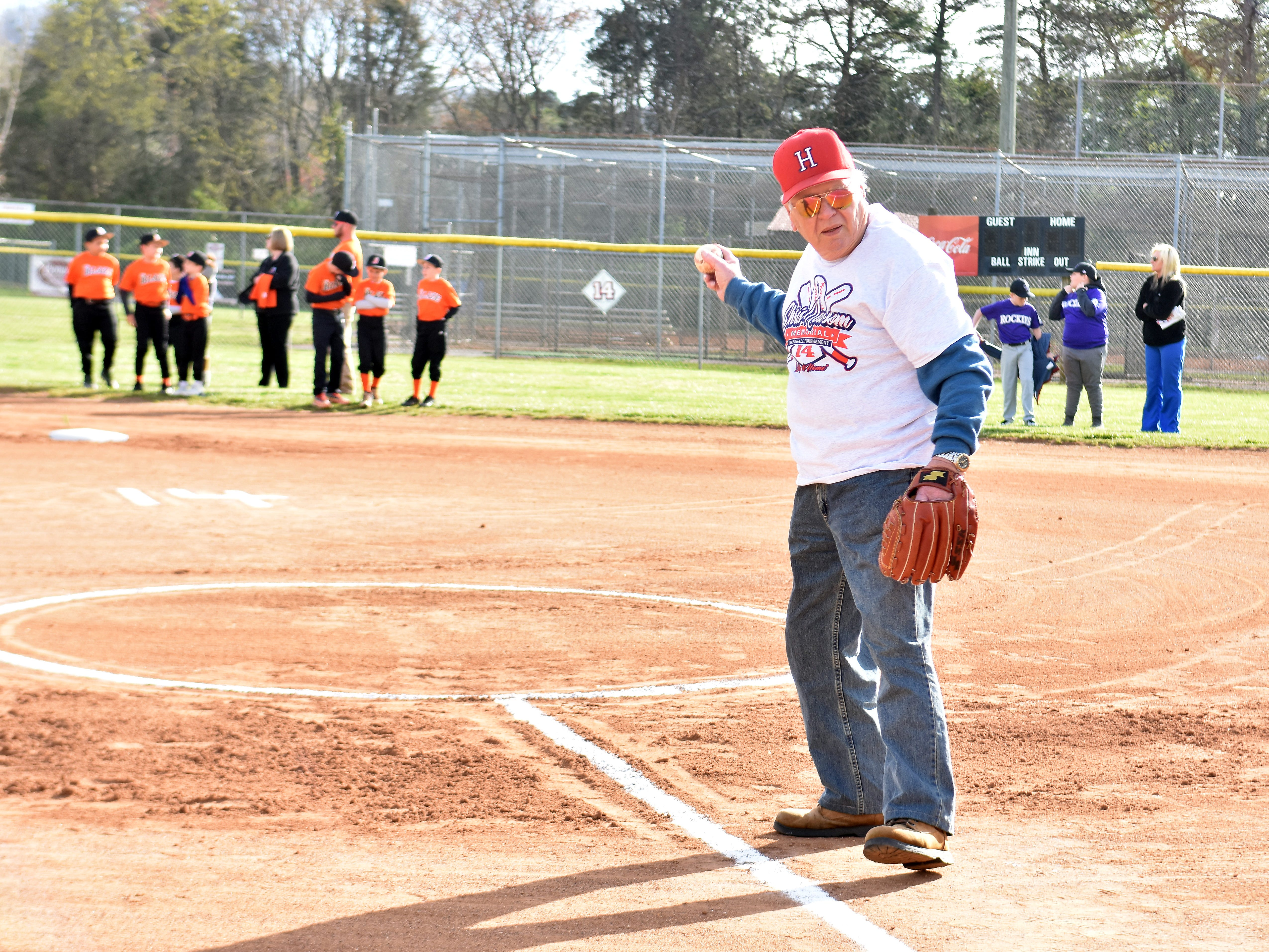 As teams begin to arrive at Halls Community Park on Monday, April 1, Hugh Newsom warms up his arm in anticipation of throwing out the first pitch of the 12th annual Chris Newsom Memorial Tournament.
