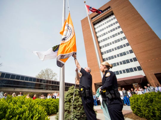 "Sgt. Christopher Oldacre and Officer Kristen Burkhart raise a ""Donate Life"" flag at the Flag Circle at UT Medical Center in Knoxville on Thursday, April 4, 2019."