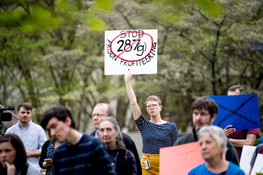 Abby Wintker, of Knoxville, holds a sign at a rally organized by AKIN against the Knox County Sheriff's Department participation in 287(g) outside of the City County Building in Knoxville, Tennessee on Thursday, April 4, 2019. Around 400 collected postcards will be delivered to the sheriff's department on Friday morning.