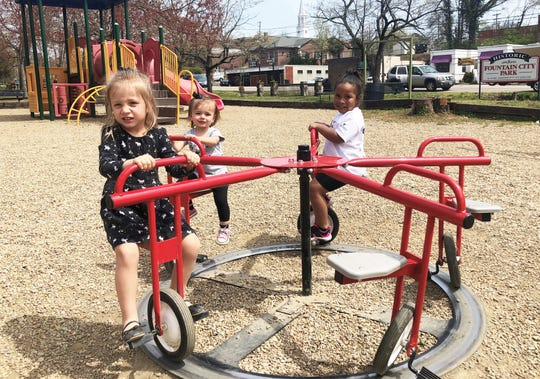 Sisters Isabella, three, and Kennedy Khan, one, enjoy the new five-seater merry-go-cycle with friend, Rae Elzy, three, on a beautiful day in Fountain City Park, April 4, 2019.