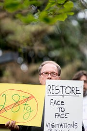 A protestor holds signs at a rally organized by AKIN against the Knox County Sheriff's Department participation in 287(g) outside of the City County Building in Knoxville, Tennessee on Thursday, April 4, 2019. Around 400 collected postcards will be delivered to the sheriff's department on Friday morning.