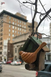 Carved birds, such as this one near the Tippecanoe County Courthouse fountain at Fourth and Main streets on Wednesday, April 3, 2019, have been showing up in trees and on shop window sills in downtown Lafayette for the past year. Downtown shop owners say it's a mystery about who has been making the birds and hanging them like ornaments in downtown.