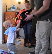 Henry Craig, left, hands his father Jacob a stuffed monster truck while his mother, Misty, looks on.
