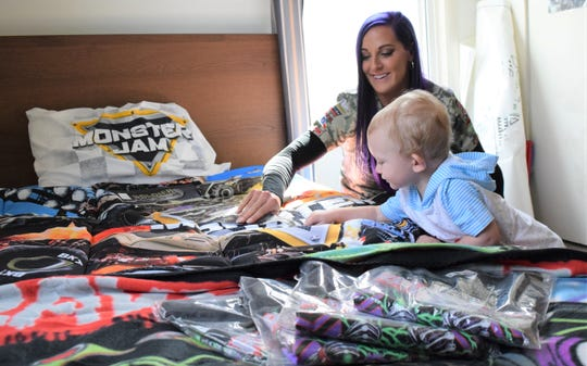 Kayla Blood, driver of the monster truck Solder Fortune, shows Henry Craig some goodies as part of a room makeover with Operation Homefront.
