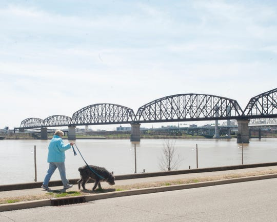 A woman walks her dog along Riverside Drive in Jeffersonville. Behind her is the Big Four pedestrian and bicycle bridge that spans the Ohio River between Louisville and Jeff.01 April 2019